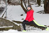 Woman Exercising Legs Outside During Winter poster