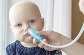 Mom Cleans Babys Nose Using A Nasal Aspirator poster