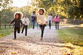 Children Running Ahead As Multi Generation Family Enjoy Autumn Walk In Countryside Together poster