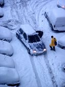 elevated view of man walking snow covered ground and parked cars