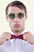 Geeky male adjusting red bow tie