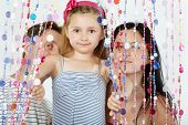 Little girl in striped sundress looks out from behind curtain of plastic beads, her parents stand be