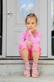 Little sorrowful girl sits on stairs near white door and thinks.