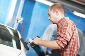 auto mechanic worker polishing car at automobile repair and renew service station shop by power buff