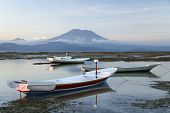 stock photo of gunung  - small boats on the reefs of nusa lembongan island indonesia with balis gunung agung volcano towering in the background