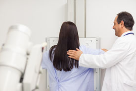 stock photo of mammography  - Doctor proceeding a mammography on a patient in an examination room - JPG