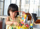 stock photo of amusement  - Little Asian girl playing with toy portrait - JPG