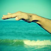 picture of a man waving free his hand in the air with the ocean at the background, with a retro effe