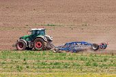 picture of cultivator-harrow  - Tractor plowing field with harrow a detail side view - JPG