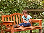 stock photo of temperance  - This 8 year old girl is cranky and grumpy while sitting outdoors on a garden bench - JPG