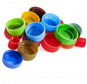 heap of multicolored used plastic bottle caps on white background