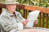 Elderly Man Reading Newspaper and Drinking Coffee