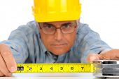 Closeup of a construction worker in hard hat using a measuring tape with the numbers facing forward. Focus is on the mans hands and tape measure.
