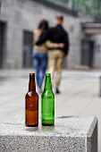 two bottles of beer and couple in the background