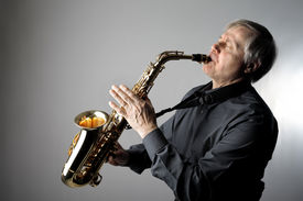 stock photo of saxophone player  - portrait of senior man playing the saxophone - JPG