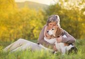 Active senior woman hugs dog poster