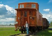 pic of caboose  - A train caboose shot on a partly cloudy day along with a young man to show the size of it - JPG