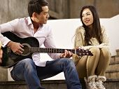 Young Lovers Playing Guitar And Singing
