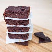 stock photo of brownie  - Fresh Homemade Vegan Chocolate Brownies stacked separated with parchment paper with two pieces of dark chocolate on the side against a beige background