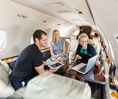 Business people having discussion over laptop on private jet