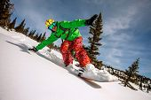 foto of snowboarding  - Snowboarder doing a toe side carve with deep blue sky in background - JPG