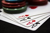 stock photo of poker hand  - Cards laying around with poker chips on top - JPG