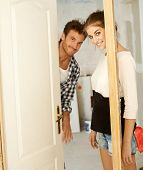 Young couple looking through door-case in new home under renovation.