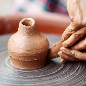 picture of molding clay  - Potter hands making in clay on pottery wheel - JPG