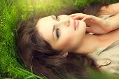 Beauty woman lying on the field and dreaming. Beautiful Girl lying on the meadow. Enjoying nature. G