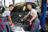 Two cheerful mechanic fixing car in a workshop