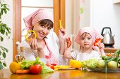 Kid Girl And Her Mother Cooking In Kitchen At Home