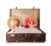 Isolated shot of retro suitcase with accessories on beach