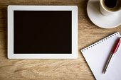 stock photo of web surfing  - Tablet with notebook on wooden table - JPG