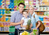 Half-length portrait of family in the shop. Son keeps pineapple over the shopping trolley full of fo