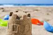 closeup of a sandcastle and some toy shovels on the sand of a beach