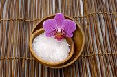 Pink orchid with salt in bowl and mat texture