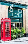 Red Phone Booth By Green Wall