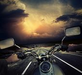 Rider on the motorcycle moving towards dark storm clouds