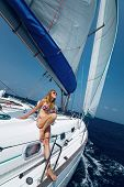 Young smiling lady relaxing on deck of the yacht during sailing