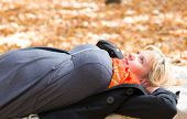 pregnant woman lay in autumn park
