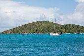 Catamaran In Blue Water By Green Hills