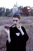 stock photo of evil queen  - evil queen with an apple in the field - JPG