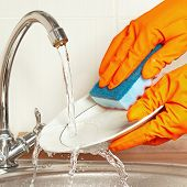 Hands in rubber gloves wash the dirty dishes under running water in kitchen