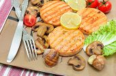 Appetizing Fried Medallions Of Salmon, Stuffed Snails With Mushrooms And Vegetables On A Plate.