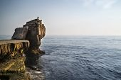 Beautiful Rocky Cliff Landscape With Sunset Over Ocean With Undientified People On Cliff Top