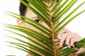 Portrait of  woman behind palm leaf.