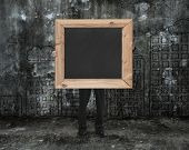 Man Holding Black Blank Chalkboard With Cityscape Doodles Mottled Wall