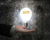Hand Holding 2015 Light Bulb Illuminated Dark Old Concrete Wall