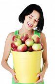 Portrait woman holding bucket full of apples.