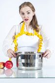 stock photo of homemaker  - Photo of surprised homemaker with pan on white background - JPG